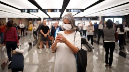 Mujer en un aeropuerto con barbijo